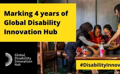 Text showing 'Marking 4 years of Global Disability Innovation Hub' is overlaid on a picture of four people sitting at a table. There is a hashtag #DisabilityInnovationDay